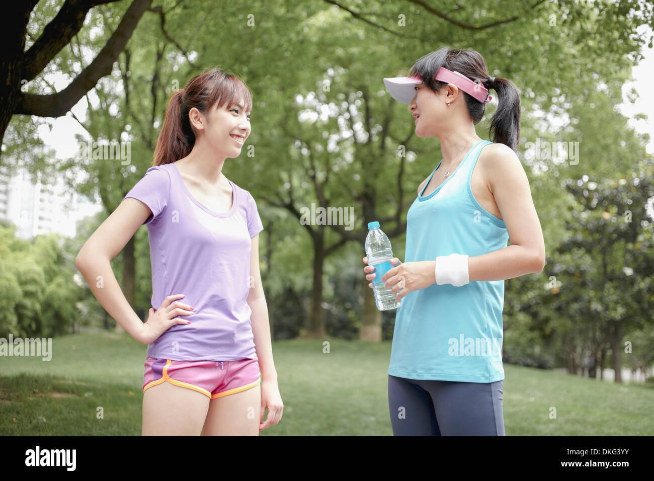 Female joggers taking a break in park - Stock Image