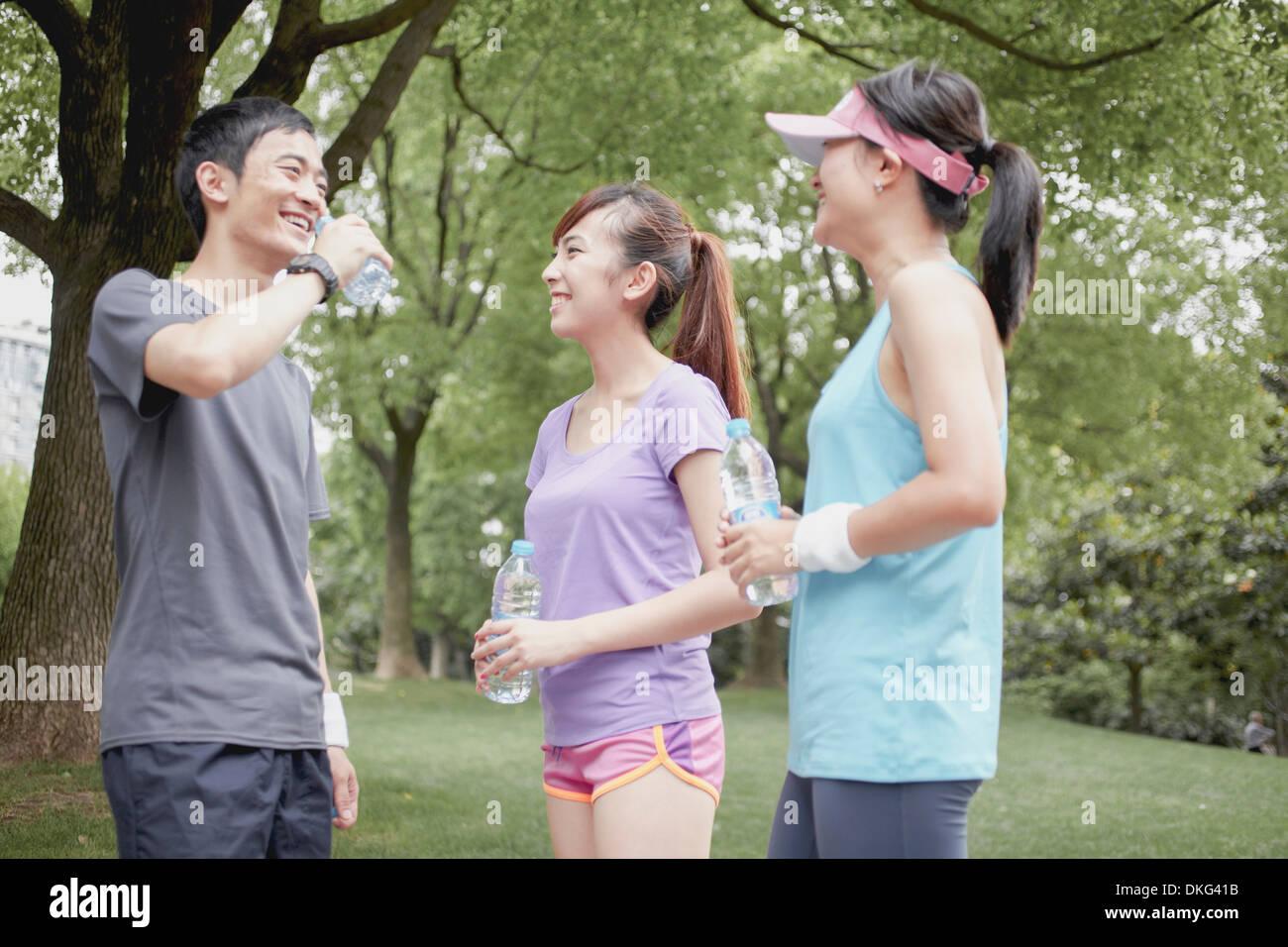 Jogger friends taking a break in park - Stock Image