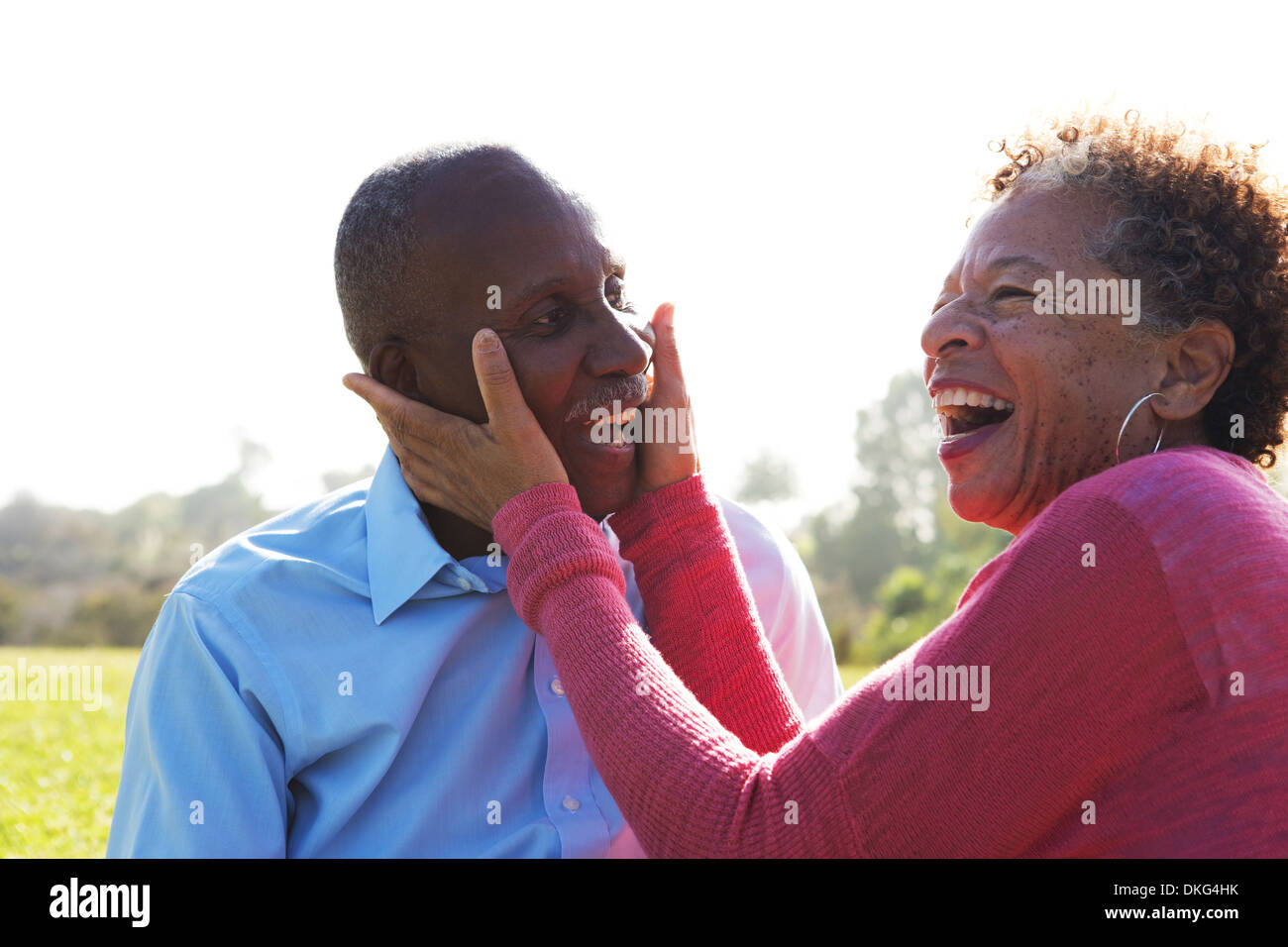 Portrait of senior couple in park, woman touching man's face - Stock Image