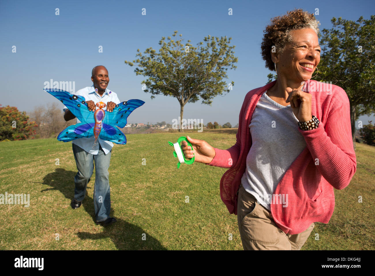 Senior couple running in park with kite - Stock Image