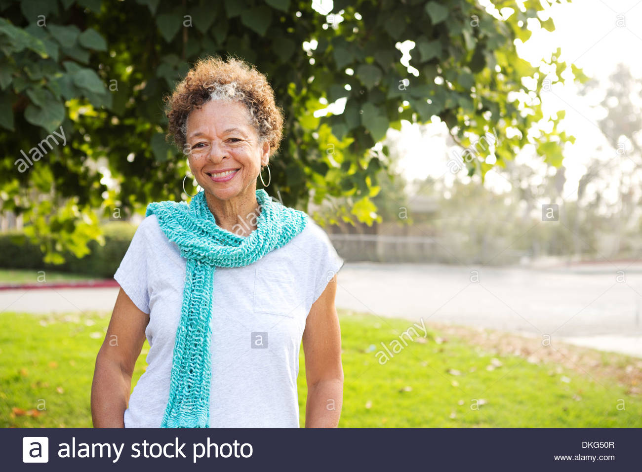 Portrait of senior woman wearing scarf in park - Stock Image