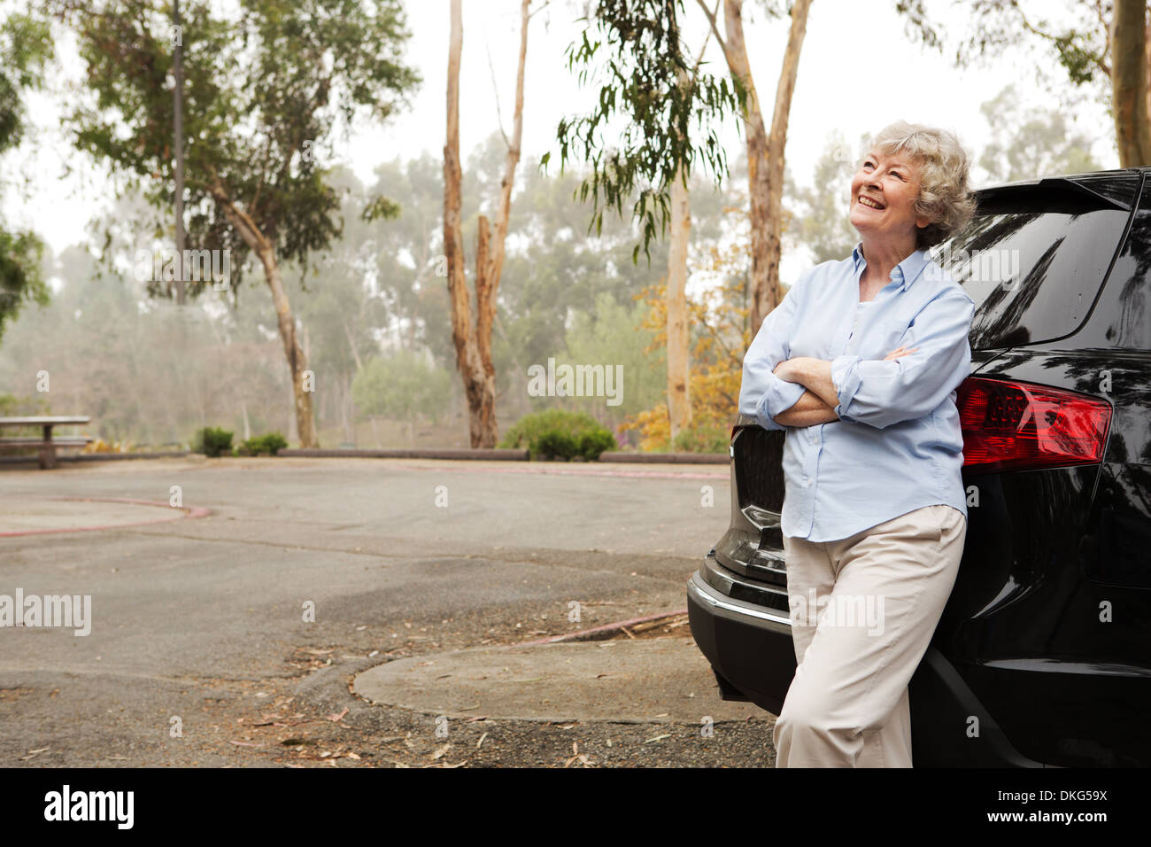 Senior woman standing against rear of black vehicle - Stock Image