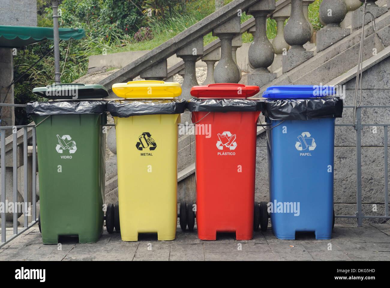 Rio de Janeiro, Brazil. Four coloured waste bins lined up: glass, paper, plastics and metal. - Stock Image