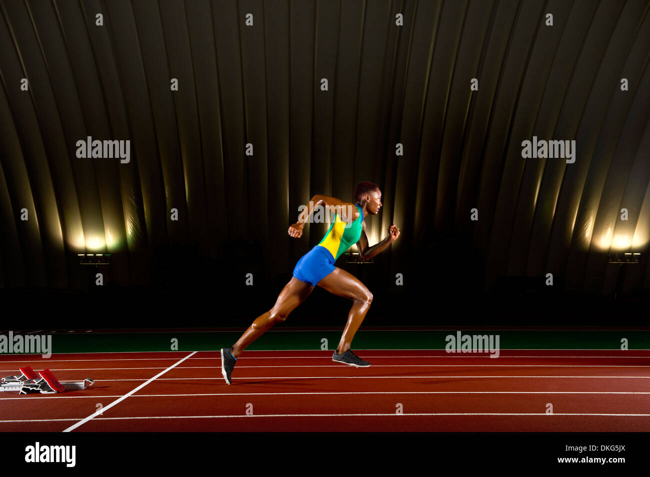 Young woman sprinting in stadium - Stock Image