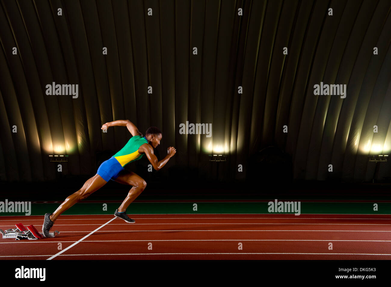 Young woman sprinting from starting blocks in stadium - Stock Image