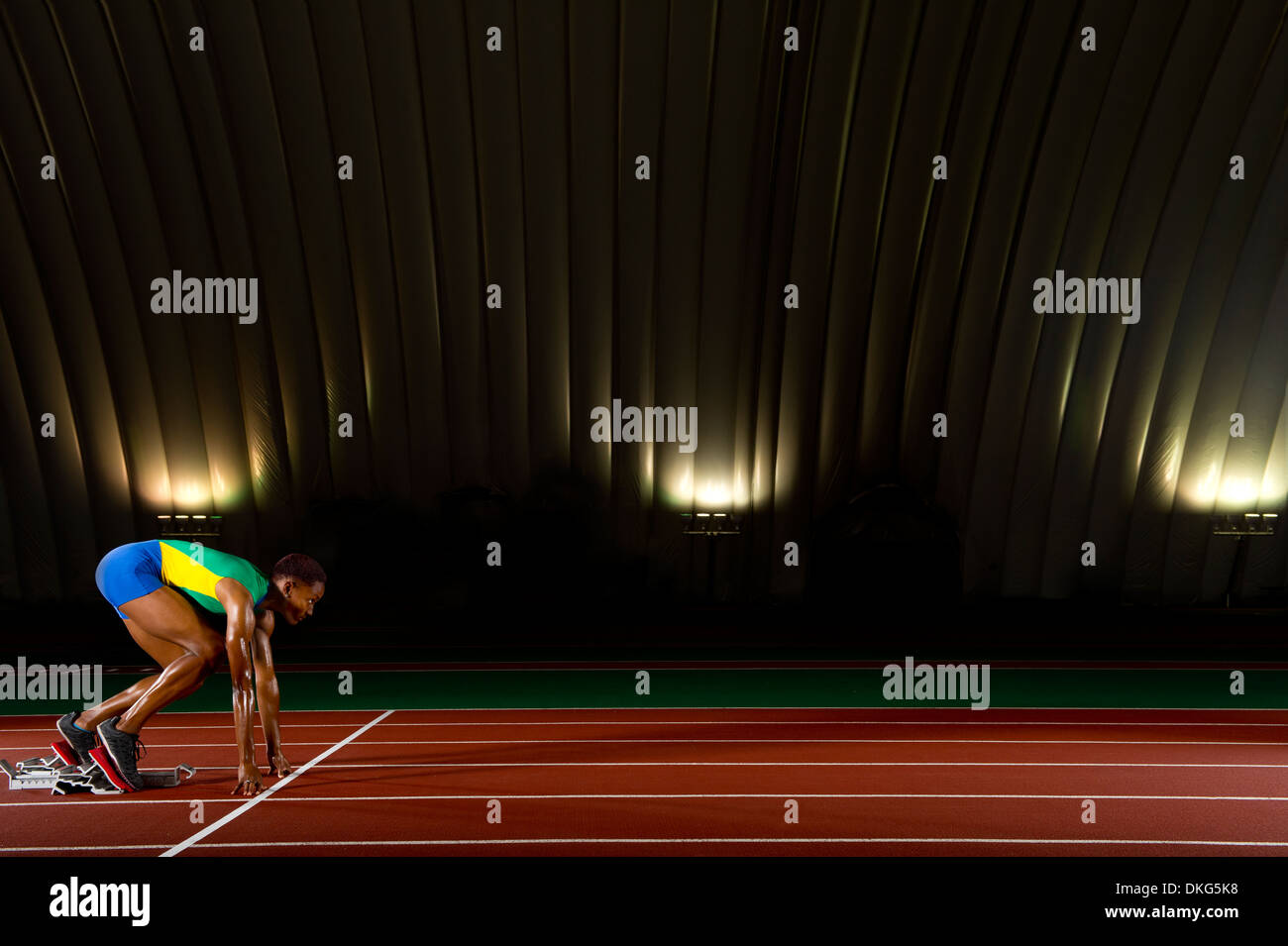 Young woman sprinting on starting blocks in stadium - Stock Image