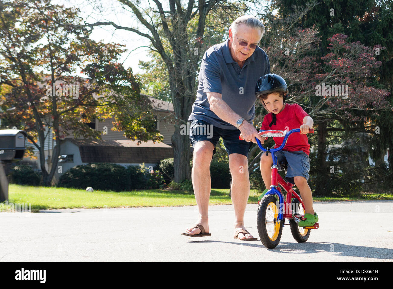 Grandfather encouraging young boy to ride bicycle - Stock Image