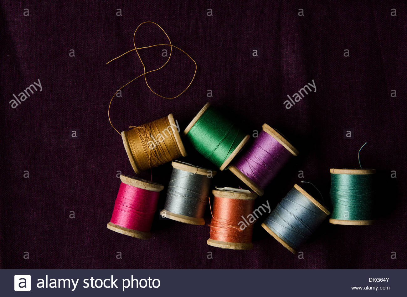 Spools of thread in different colors on black background. - Stock Image
