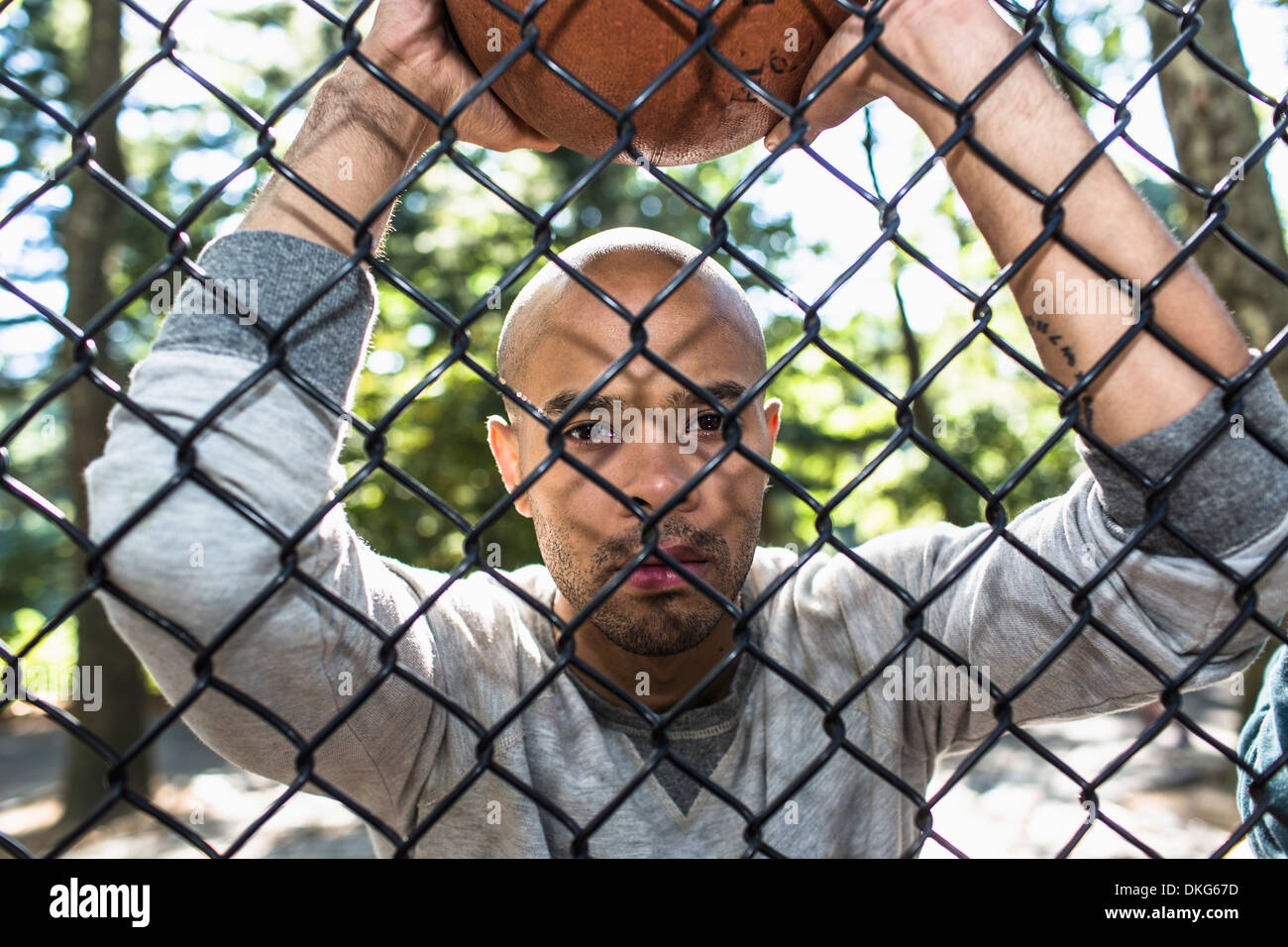 Portrait of young man holding basketball through wire fence - Stock Image