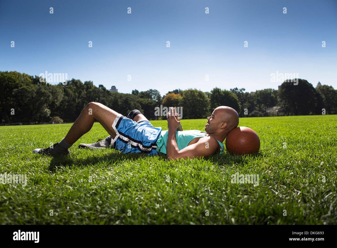 Young man lying on grass with head on basketball - Stock Image