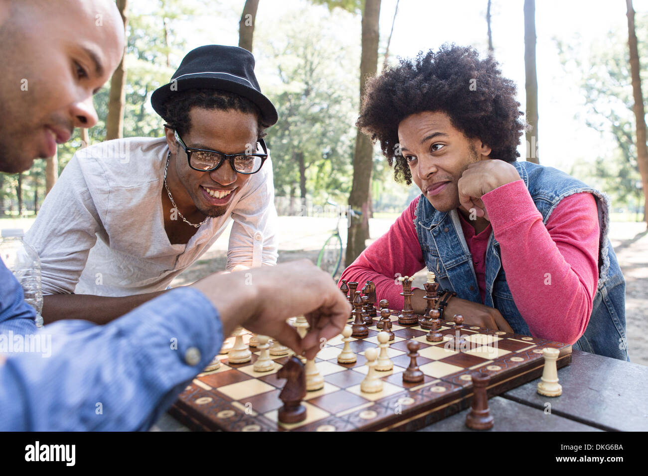 Three young men playing chess in park - Stock Image