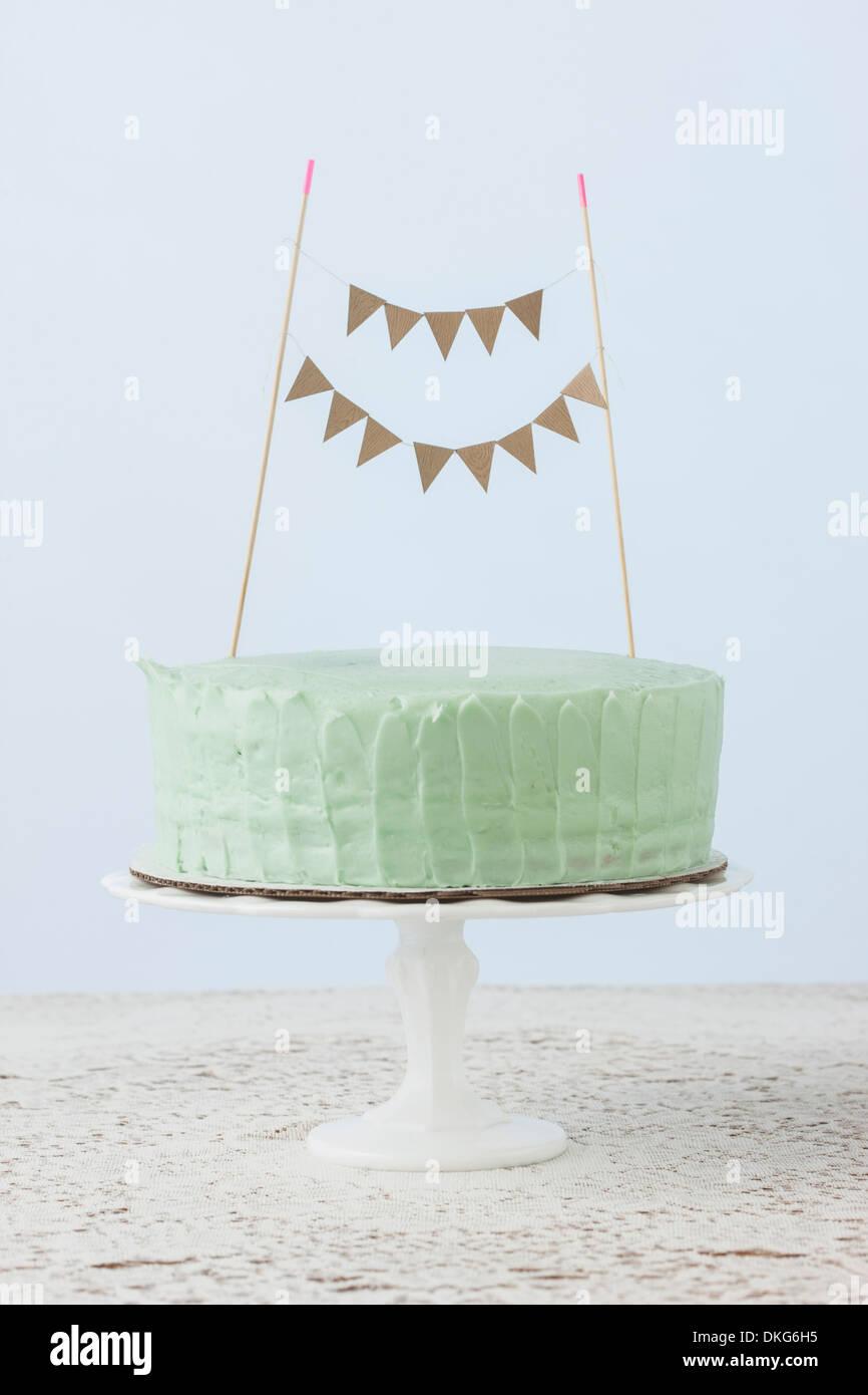 Still life of celebration cake decorated with flag bunting - Stock Image