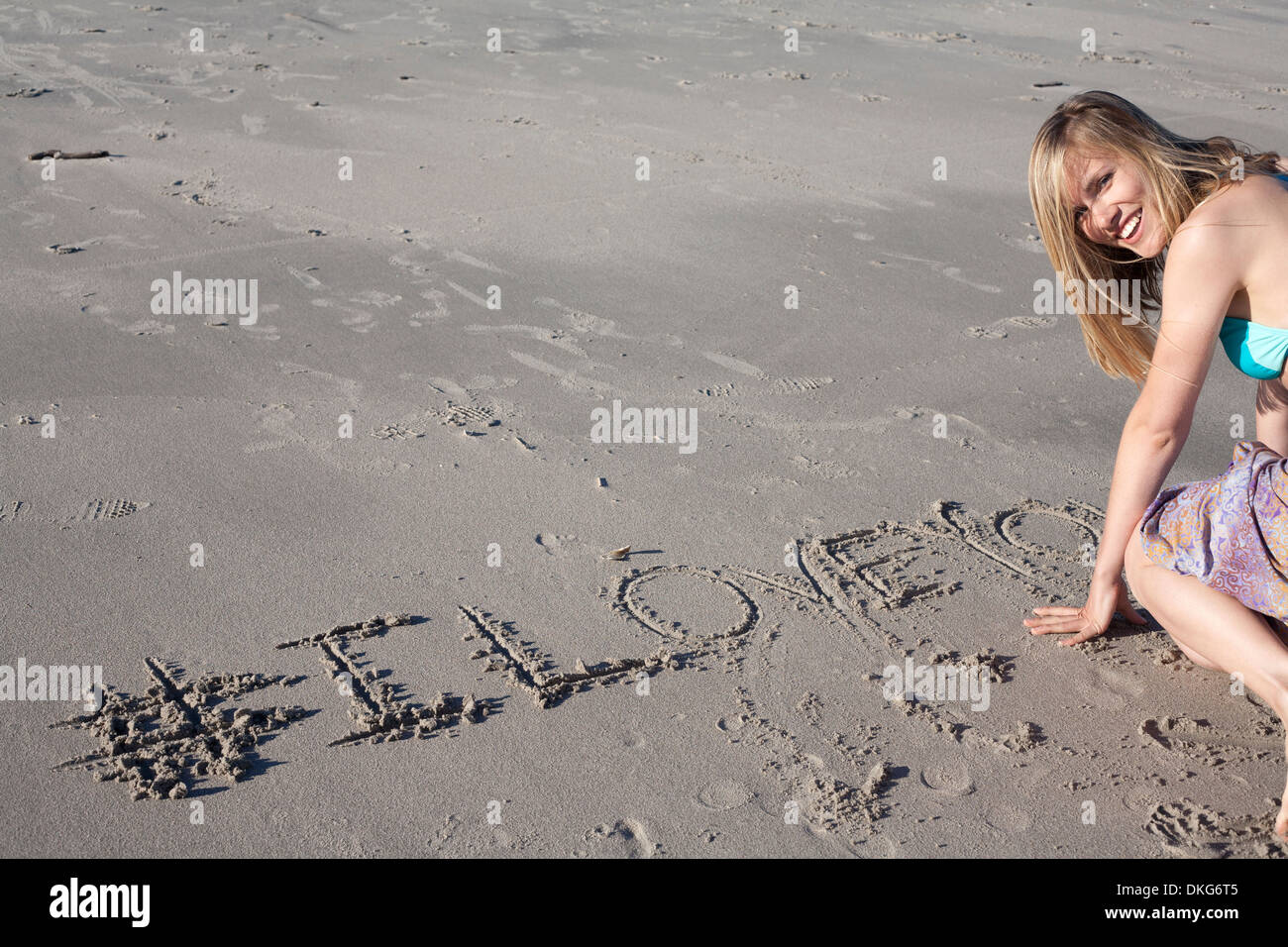 Young woman writing love message in sand, Breezy Point, Queens, New York, USA - Stock Image