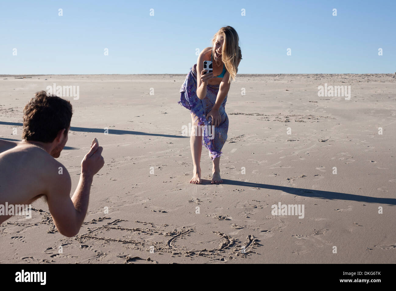 Couple writing in sand, Breezy Point, Queens, New York, USA - Stock Image