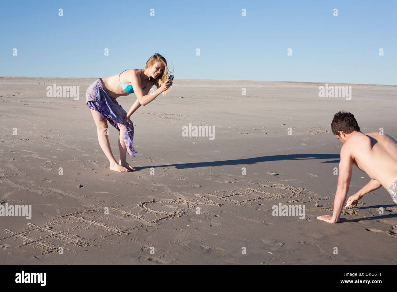 Couple writing message in sand, Breezy Point, Queens, New York, USA - Stock Image