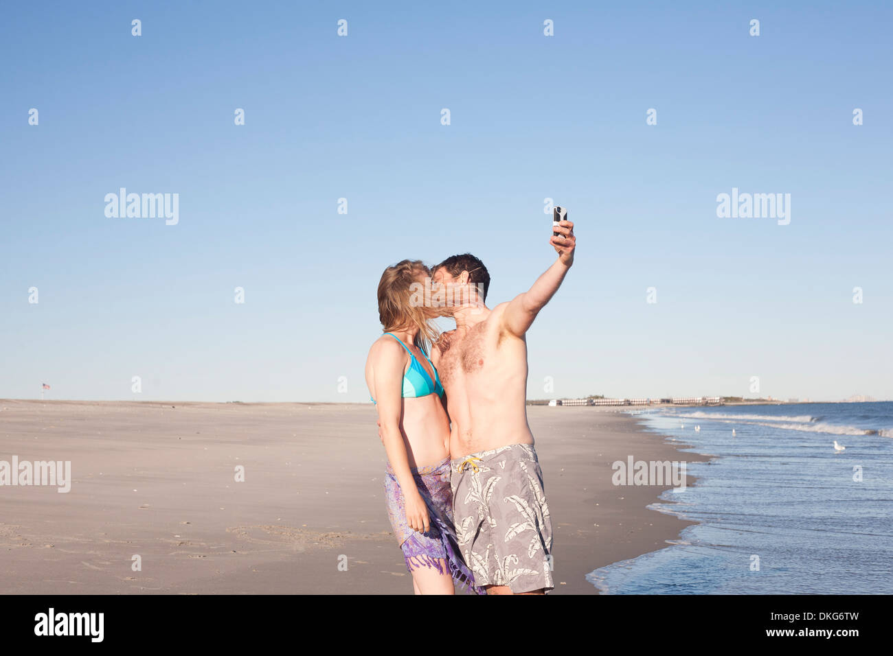 Couple taking self portrait on beach, Breezy Point, Queens, New York, USA - Stock Image