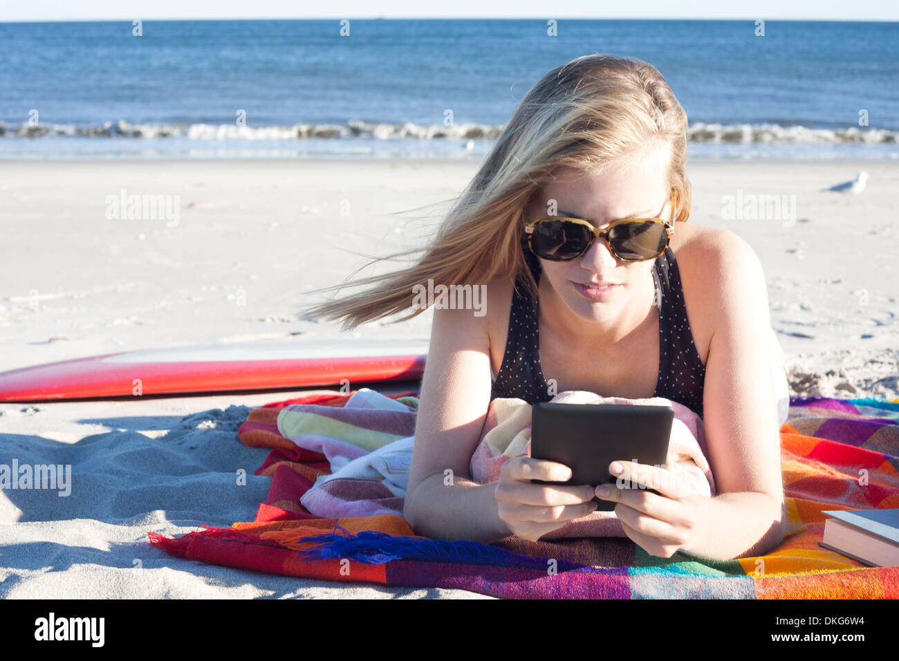 Young woman looking at digital tablet on beach, Breezy Point, Queens, New York, USA - Stock Image