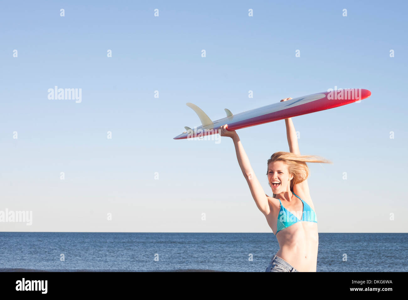 Young woman holding surfboard up, Breezy Point, Queens, New York, USA - Stock Image