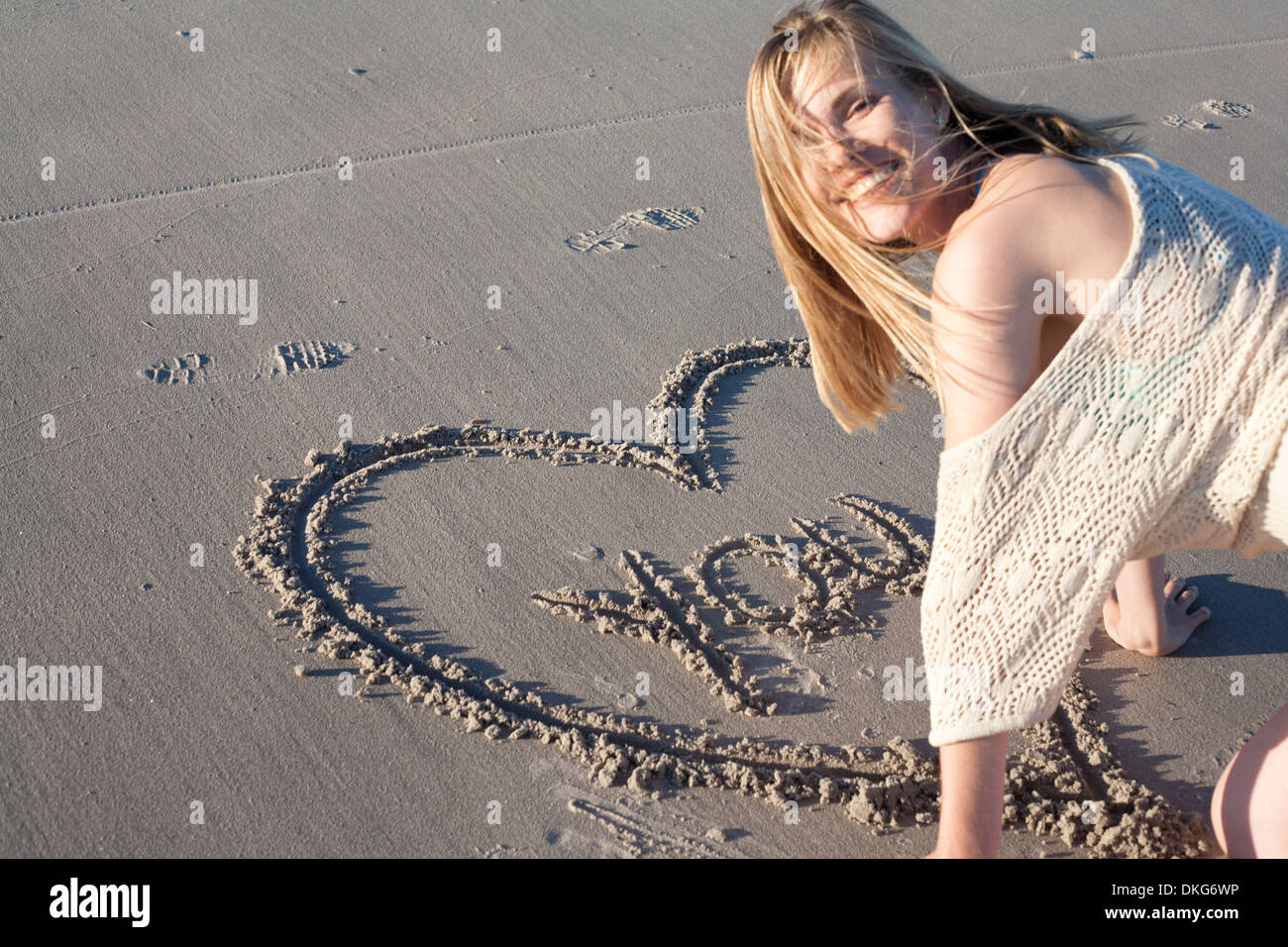 Smiling woman writing love message in sand, Breezy Point, Queens, New York, USA - Stock Image