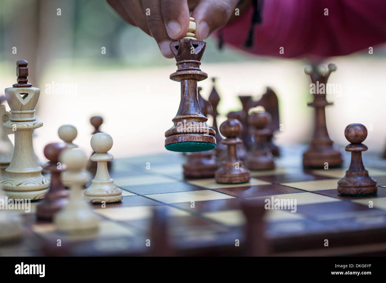 Hand moving chess piece on board, close up - Stock Image