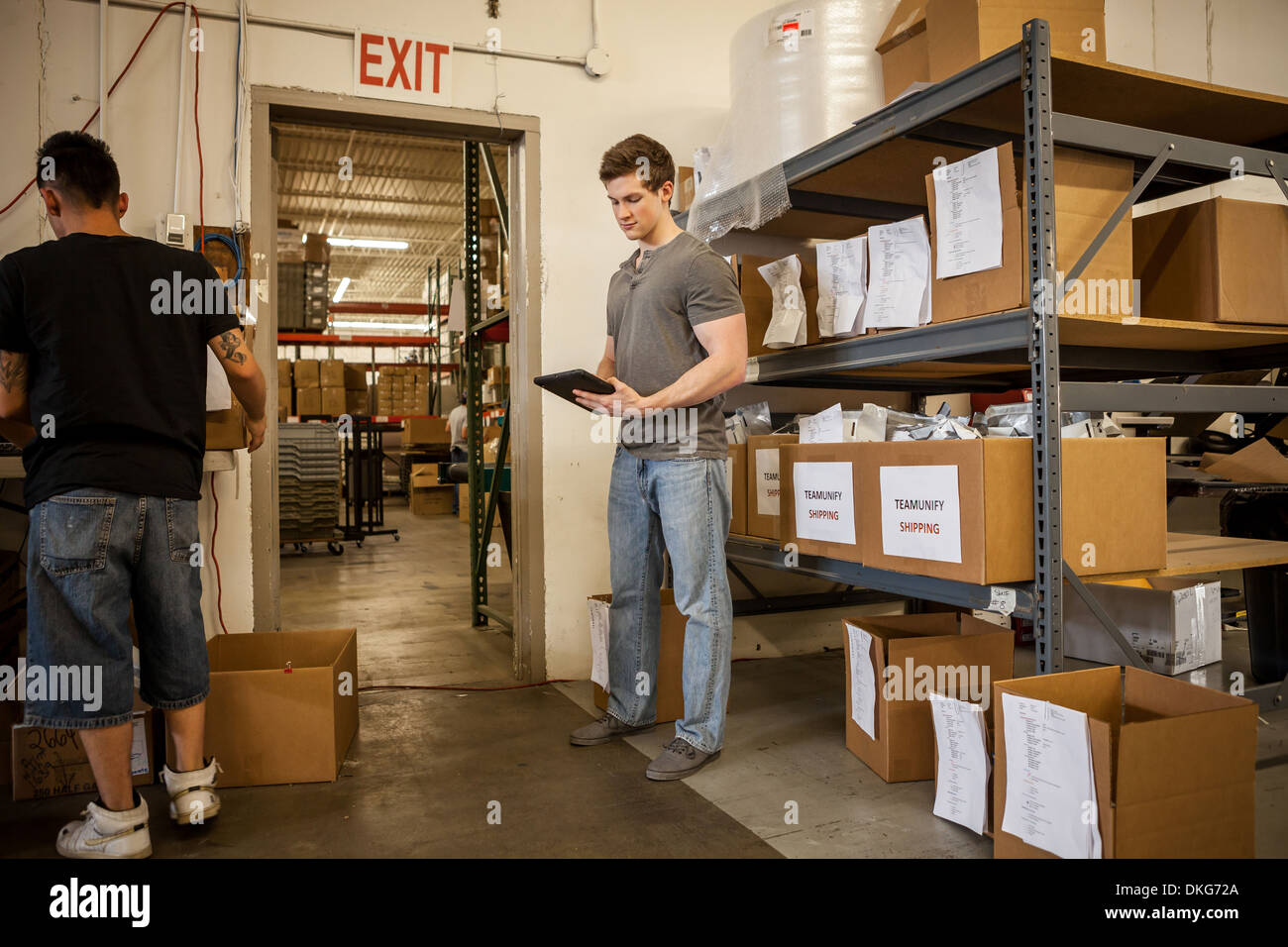 Workers in warehouse looking at paperwork - Stock Image