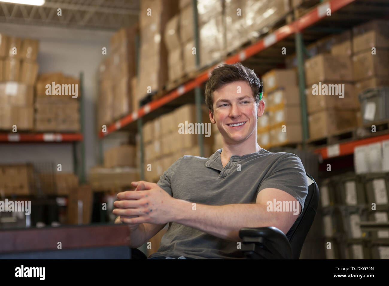 Worker sitting in warehouse - Stock Image
