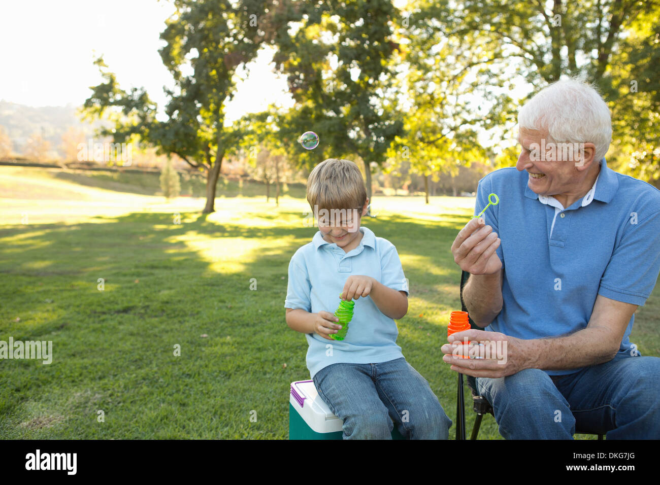 Grandfather and grandson blowing bubbles - Stock Image
