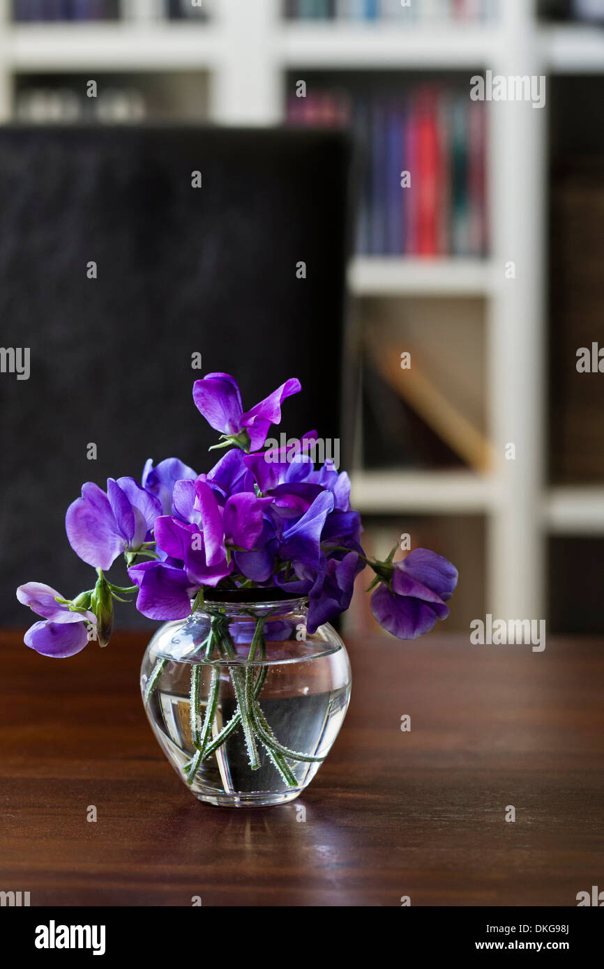 Vase with purple vech on a wooden table - Stock Image