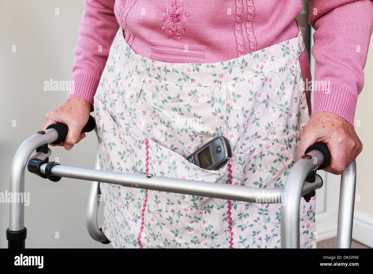 Elderly senior woman carrying a cordless phone handset in an apron pocket using a walker for support standing. England, UK, Britain - Stock Image