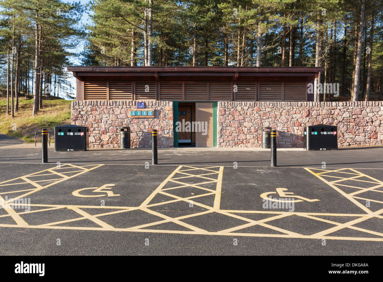 Disabled parking bays outside a toilet block in newly renovated car park in Newborough Forest Isle of Anglesey North Wales UK - Stock Image