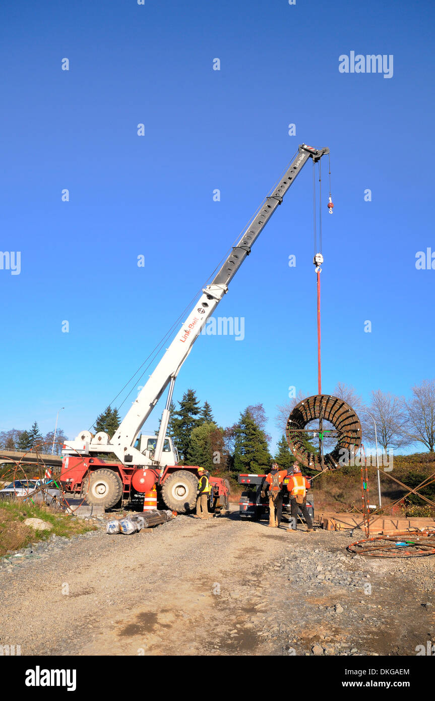 Workers offload rebar cylinder shape off flatbed truck, using a crane. - Stock Image