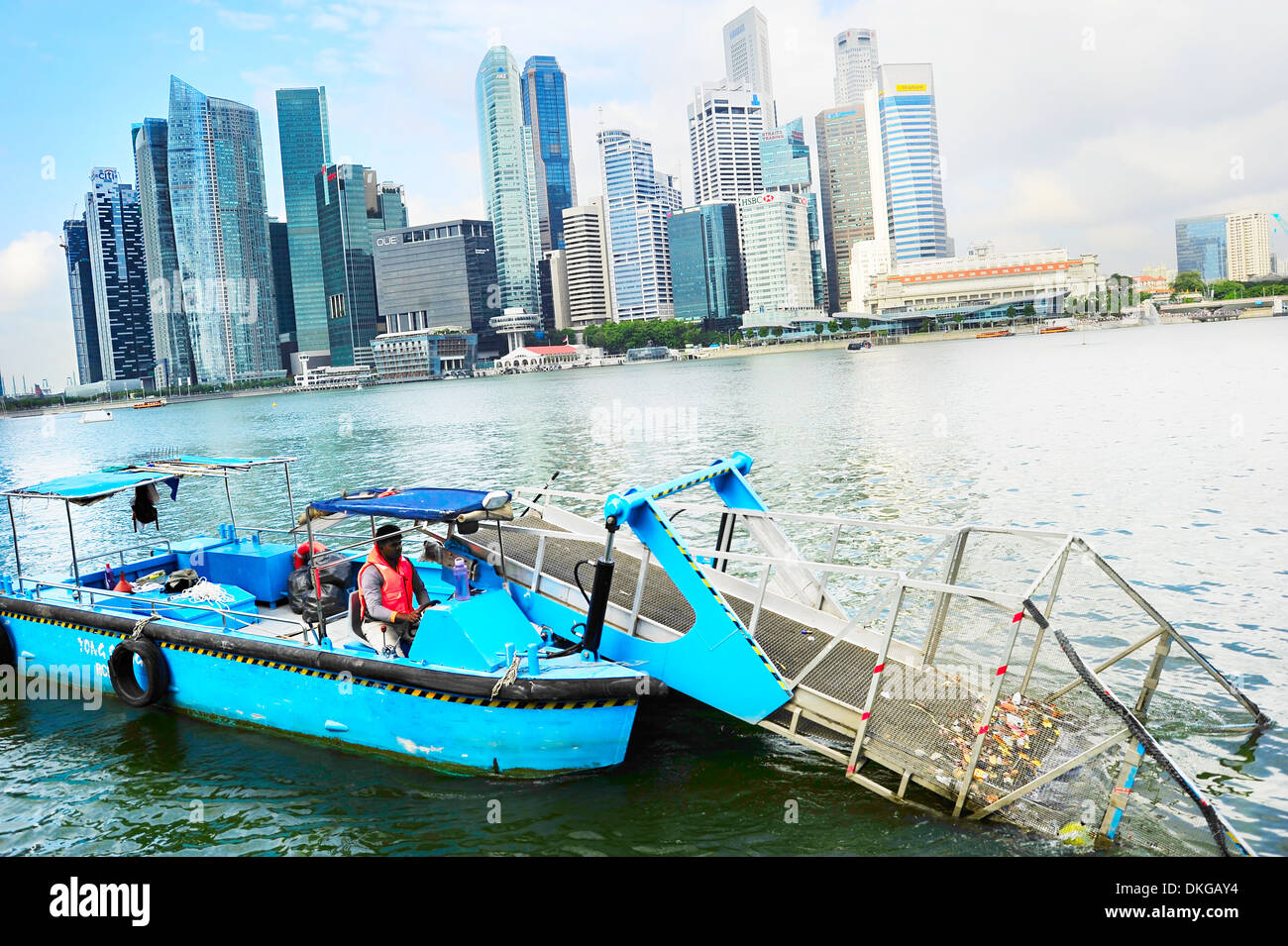 Water surface cleaning boat removing the garbage from the river in front of Singapore downtown - Stock Image