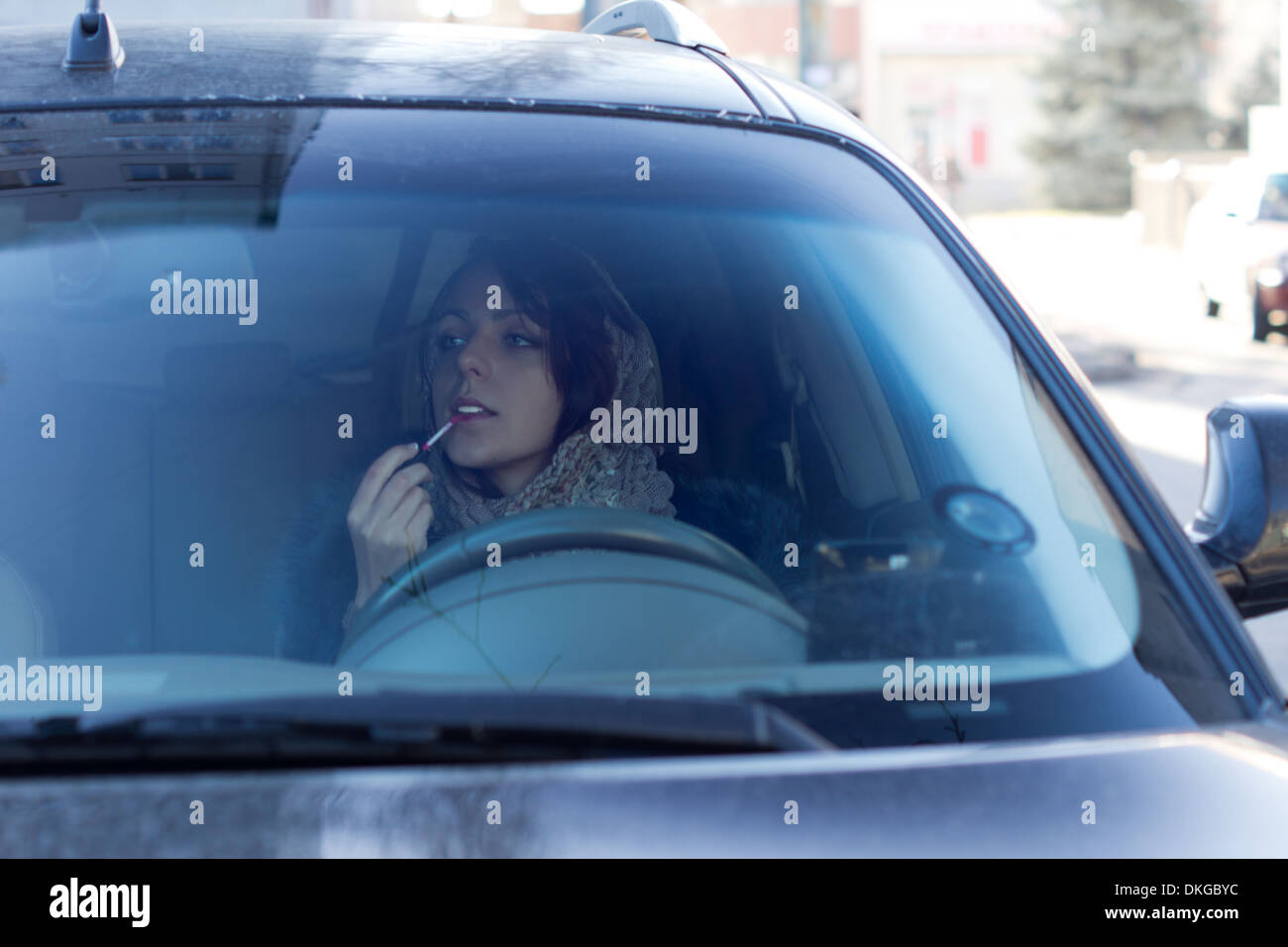 Dangerous irresponsible female driver applying her makeup using the rear-view mirror as she drives to work endangering herself and other motorists by her inattention. - Stock Image