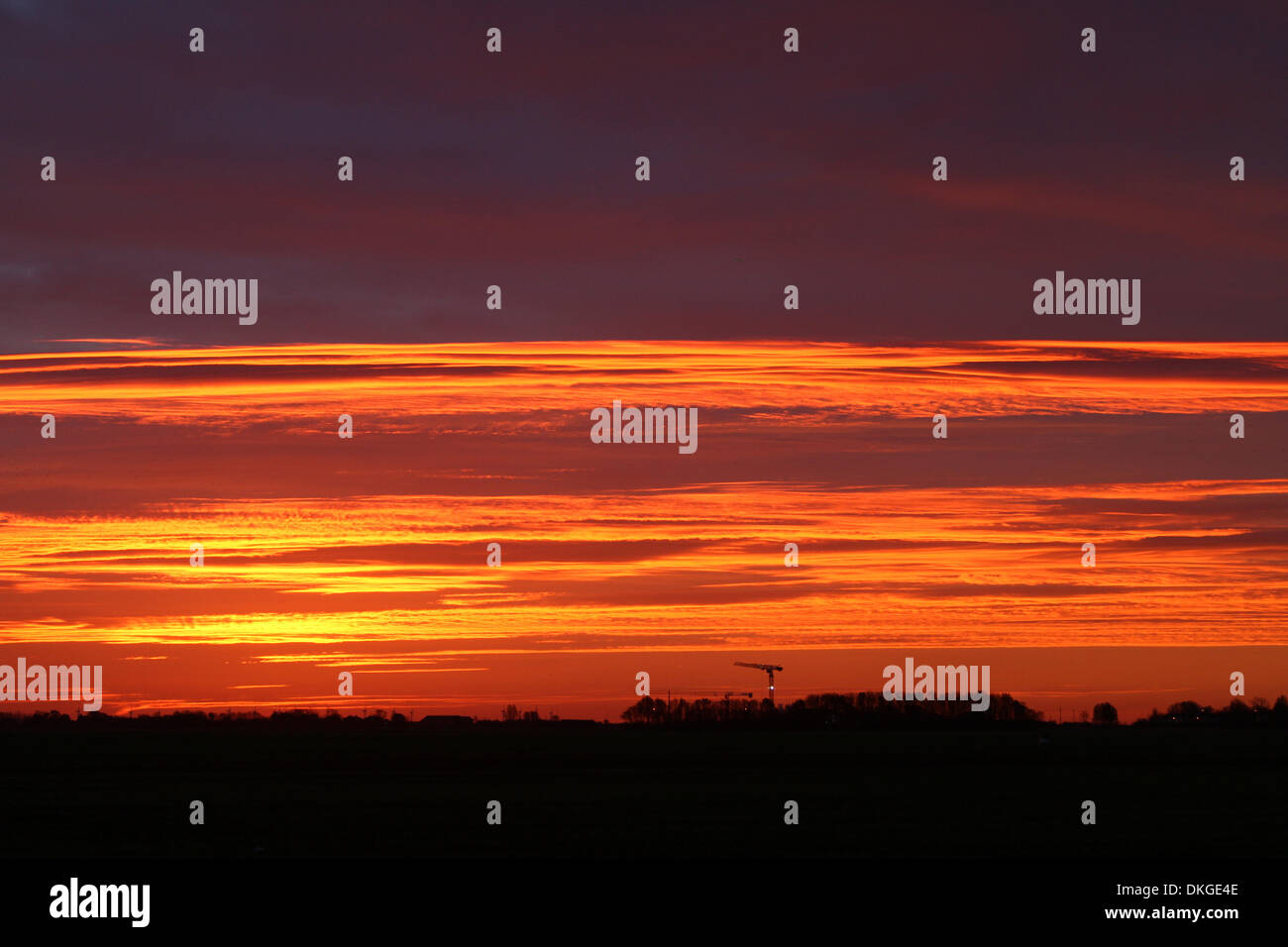 Peterborough, UK. 05th Dec, 2013. Red sky in the morning is said to be shepherds warning, as the sky looks like it's on fire, just before sunrise in Peterborough, Cambridgeshire. Storms are set to brace the eastern side of the country today with high winds and abnormally high spring tides. Credit:  Paul Marriott/Alamy Live News - Stock Image