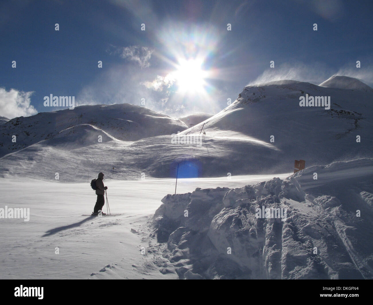 skier on a windblown snow covered piste under blue sky - Stock Image