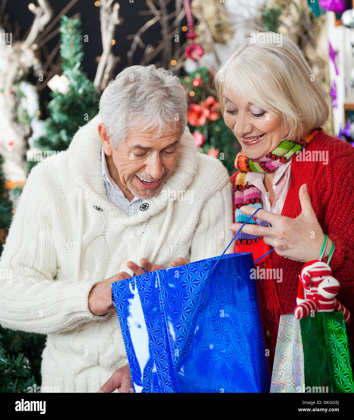 Surprised Couple Looking Into Shopping Bag - Stock Image
