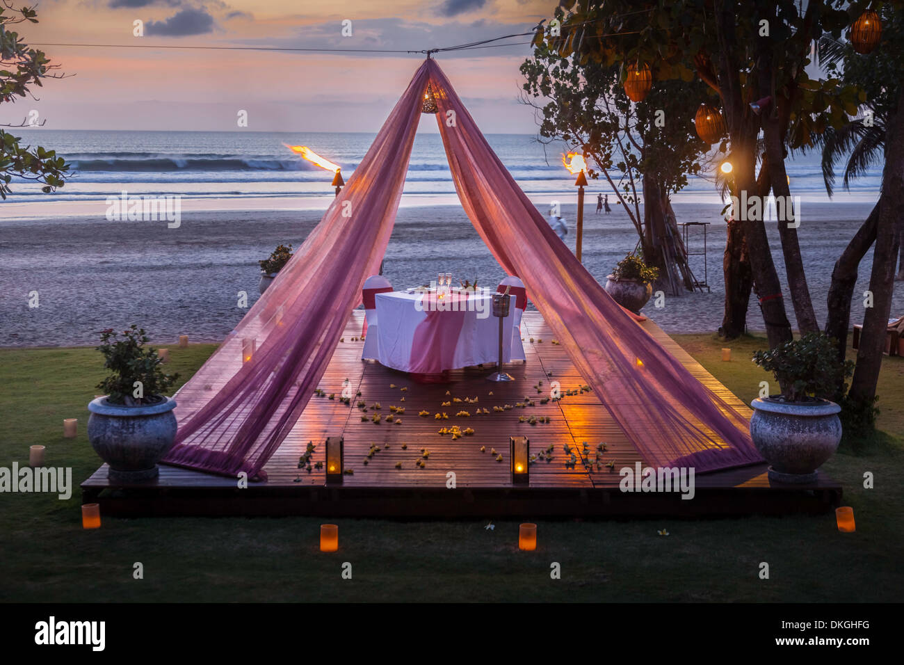 Romantic dinner table two couple Bali beach candle plates food sunset Asia pink curtain luxury service offer hotel tourist art & Romantic dinner table two couple Bali beach candle plates food ...