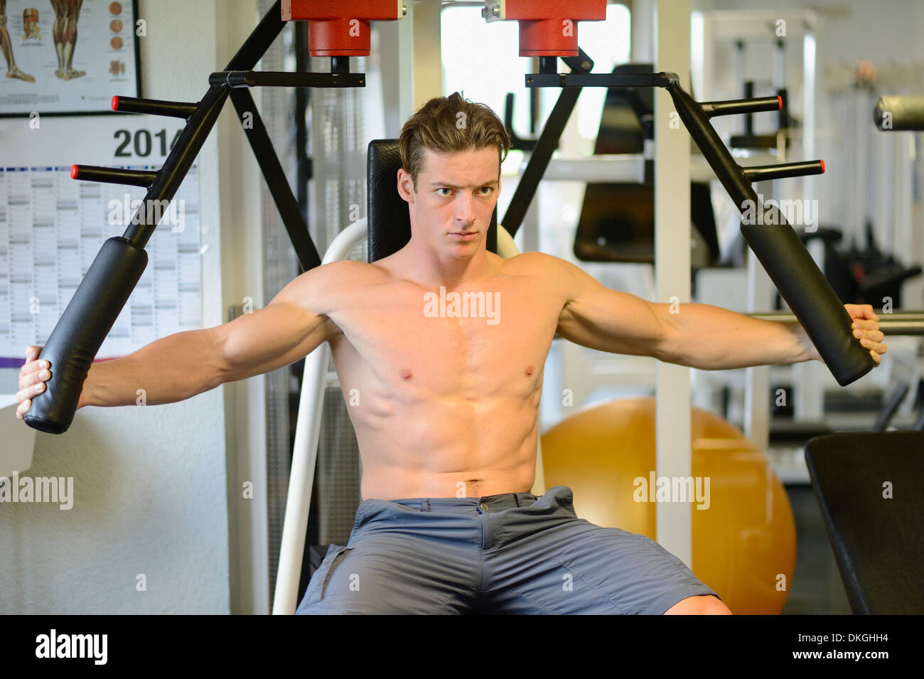 Young man exercising in fitness center - Stock Image