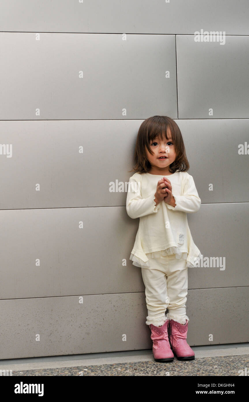 A two-year-old MR mixed race female laughs while having her picture taken. She has brown hair, is wearing a white outfit - Stock Image