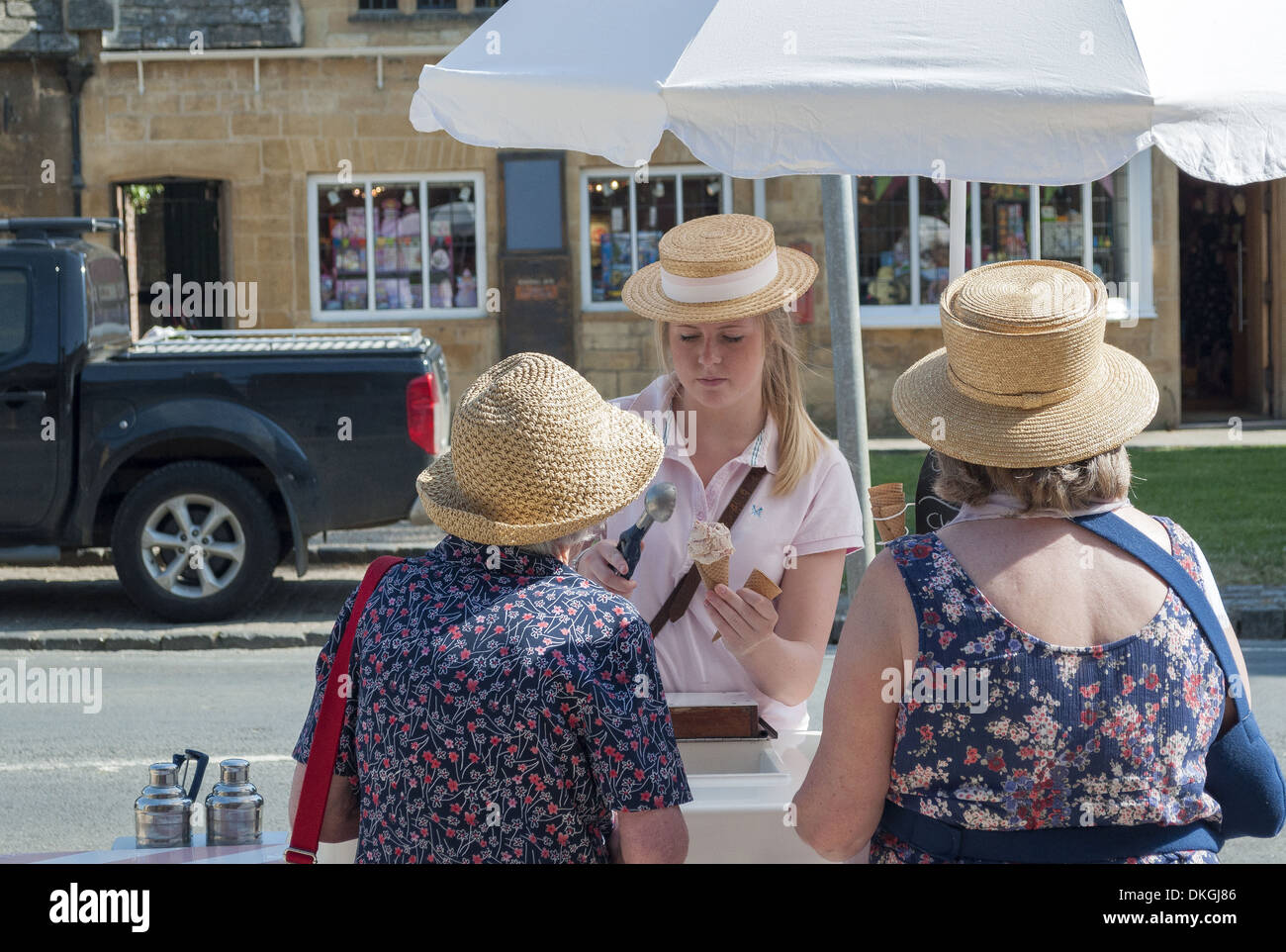 02638f1652b51 Girl serving ice cream on a hot summers day to two ladies in straw summer  hats in Broadway Village