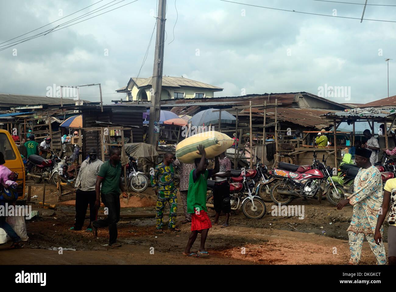 people walking open air outdoor market shops stalls ibadan lagos nigeria buying selling buy sell - Stock Image