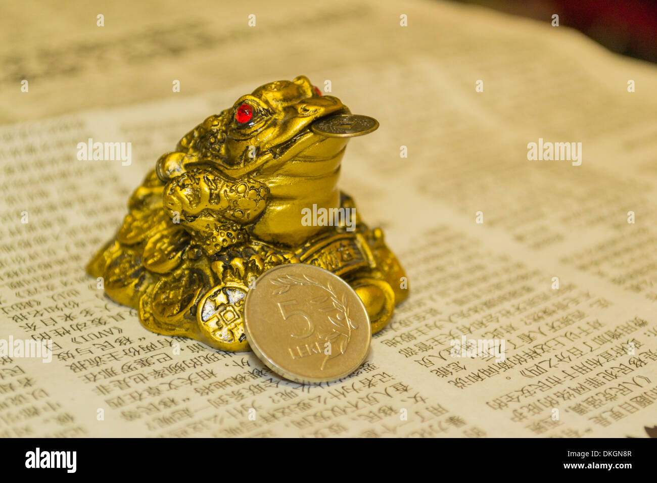 Money toad on Chinese newspaper holding a five Albanian Lek coin (ALL) - Stock Image