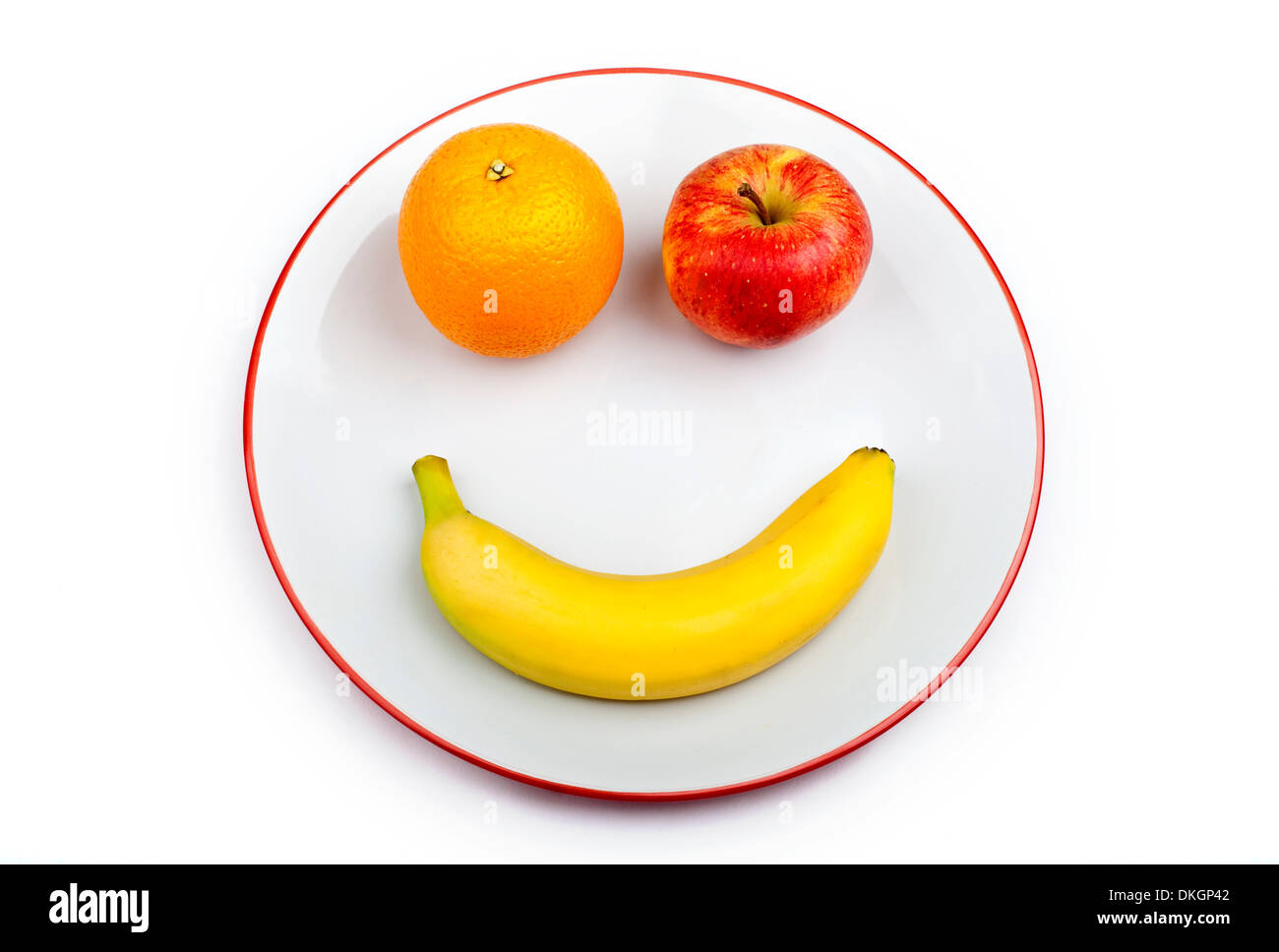 Three different pieces of fruit making up a smiling face on a plate over a white background. - Stock Image