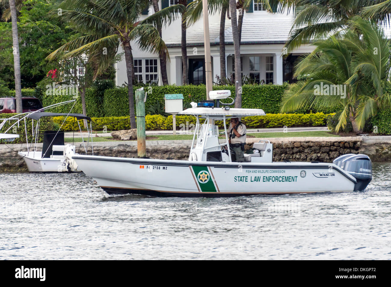 Male officer with Fish and Wildlife Commission driving Boston Whaler State law enforcement boat on Intracoastal Stock Photo