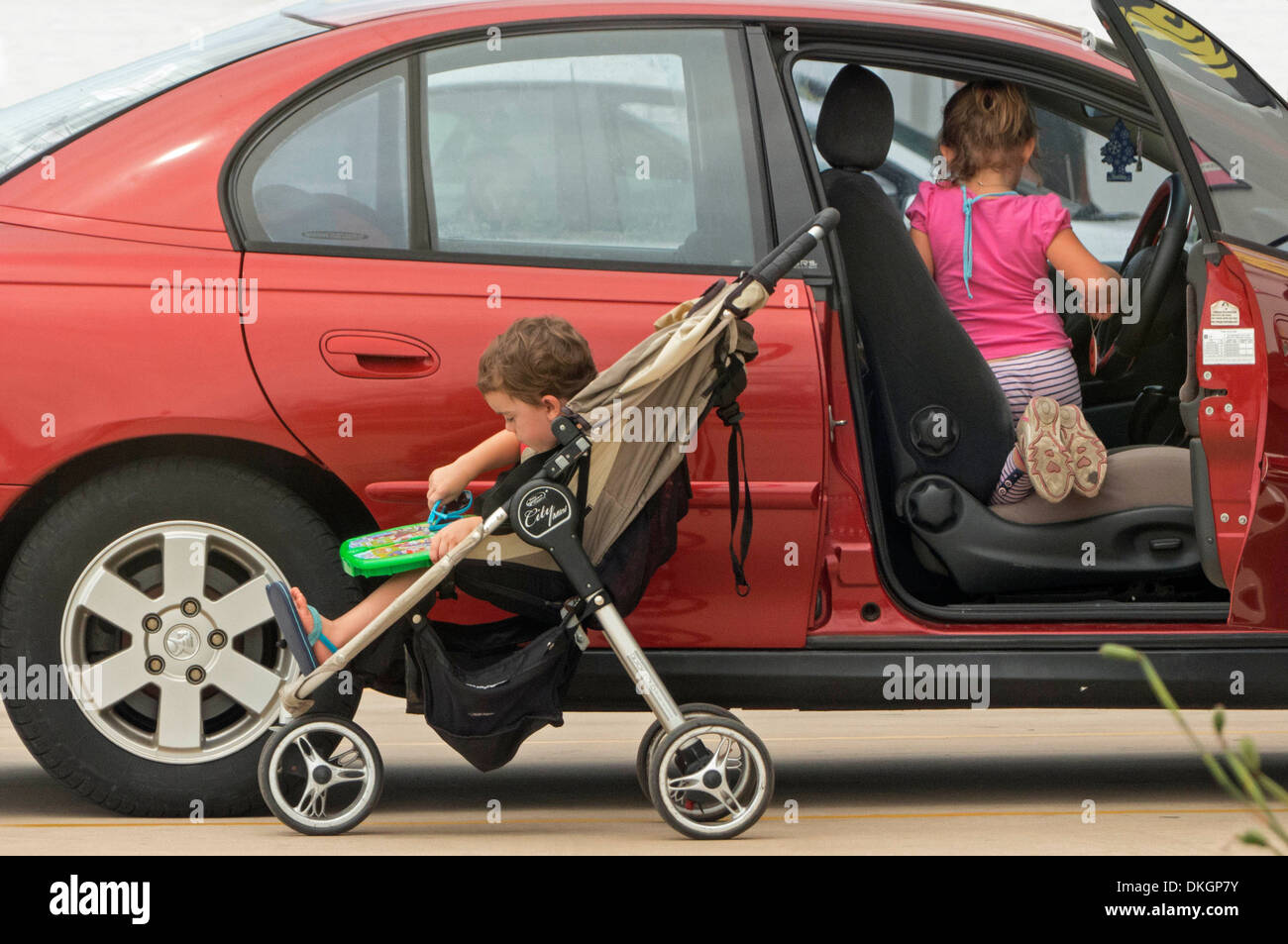Young children left unattended in and beside open door of car in shopping centre car park - Stock Image