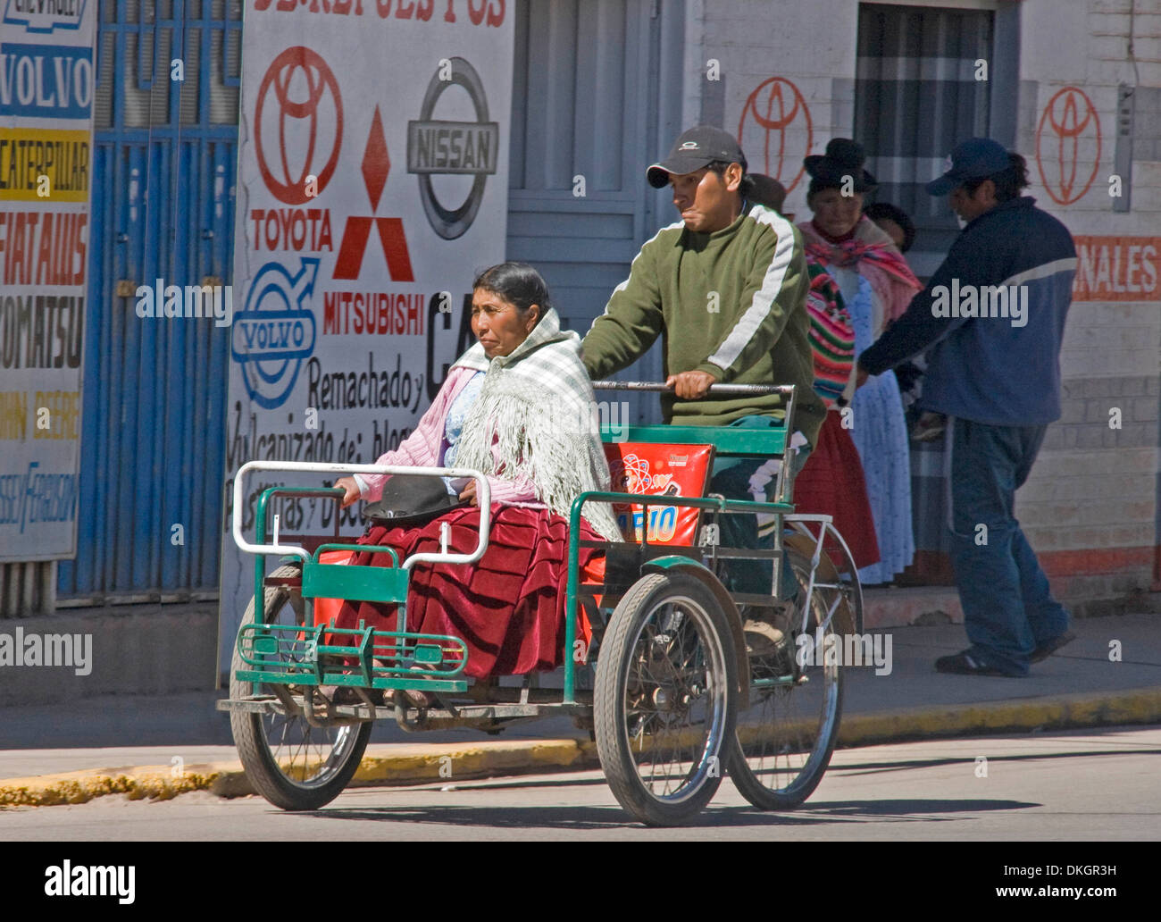 Indigenous woman in traditional dress riding in bicycle taxi with man  pedalling along city street in