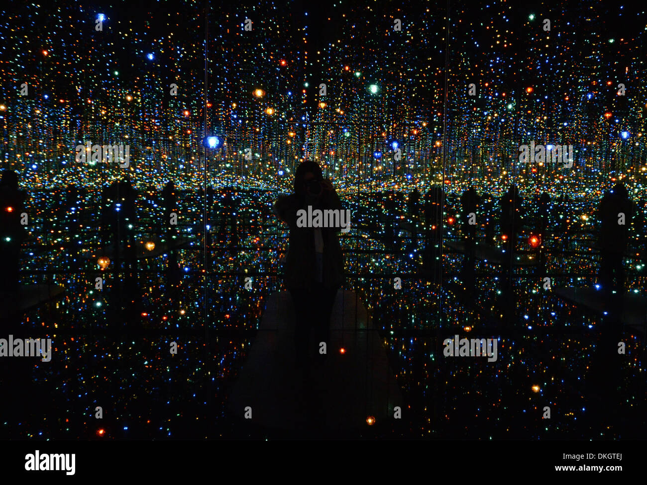 New York, USA. 5th December 2013. A visitor is reflected in the mirror while visiting the 'Infinity Mirrored Room - The Souls of Millions of Light Years Away', an installation art by Japanese artist Yayoi Kusama in New York, the United States of America, on Dec. 5, 2013. Two mirrored infinity rooms by Japanese artist Yayoi Kusama are currently on display at the David Zwirner gallery in New York City. The infinity room 'Love Is Calling' is filled with brightly-colored and polka-dotted inflatable appendages. Credit:  Xinhua/Alamy Live News - Stock Image