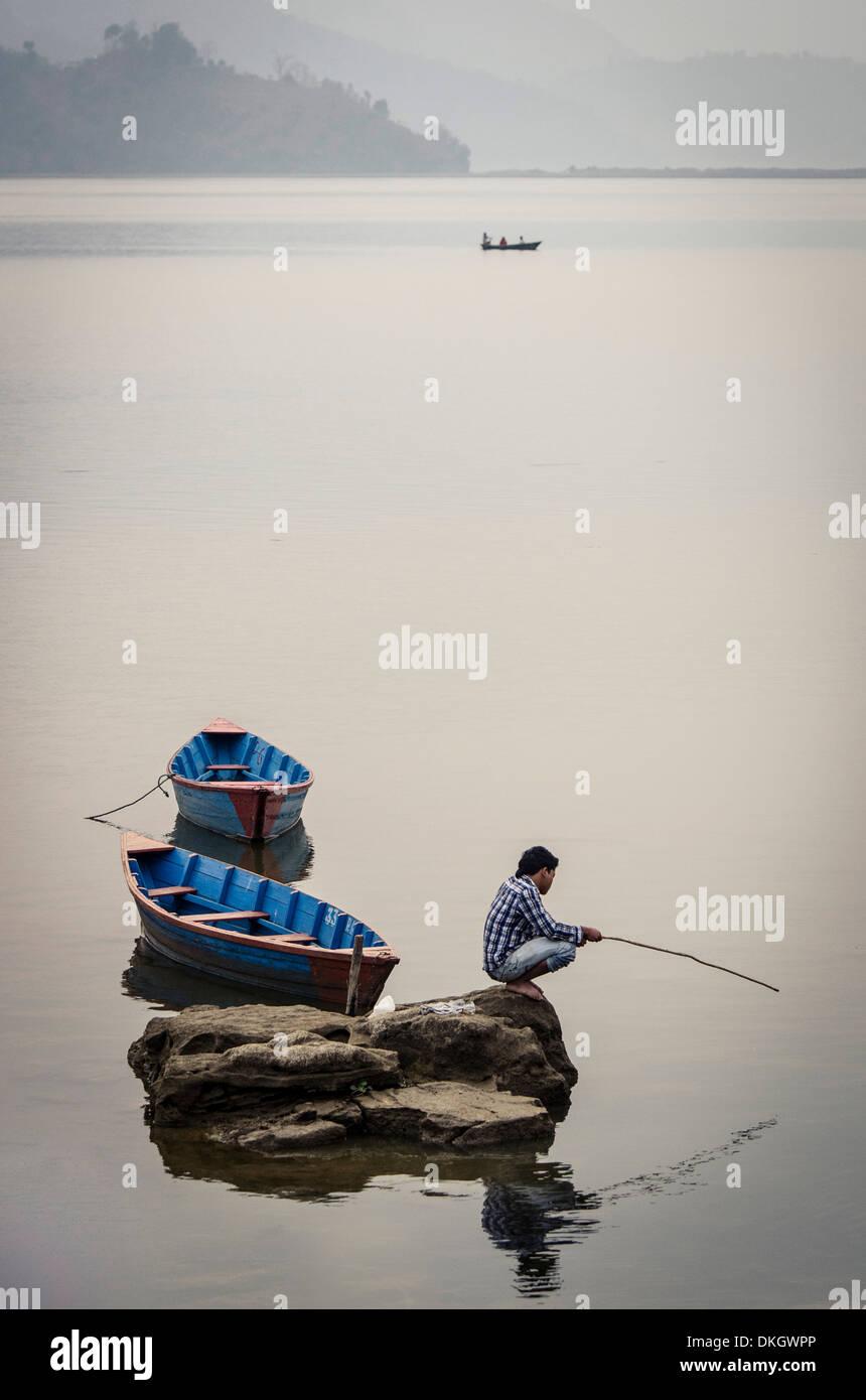 A man fishing on Phewa Tal (Phewa Lake), Pokhara, Nepal, Asia - Stock Image