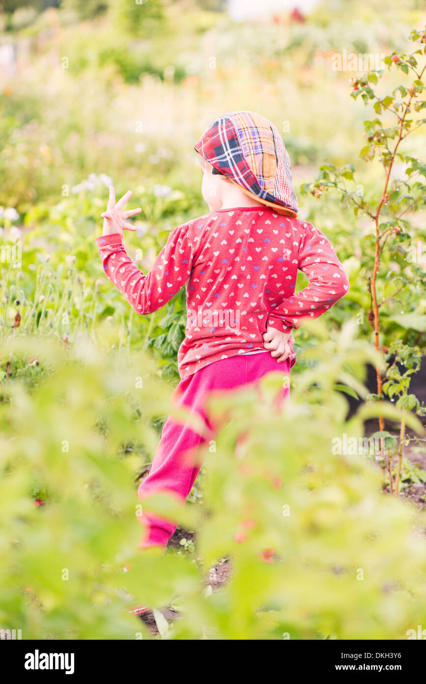 Back view of young child standing in garden studying her hand - Stock Image