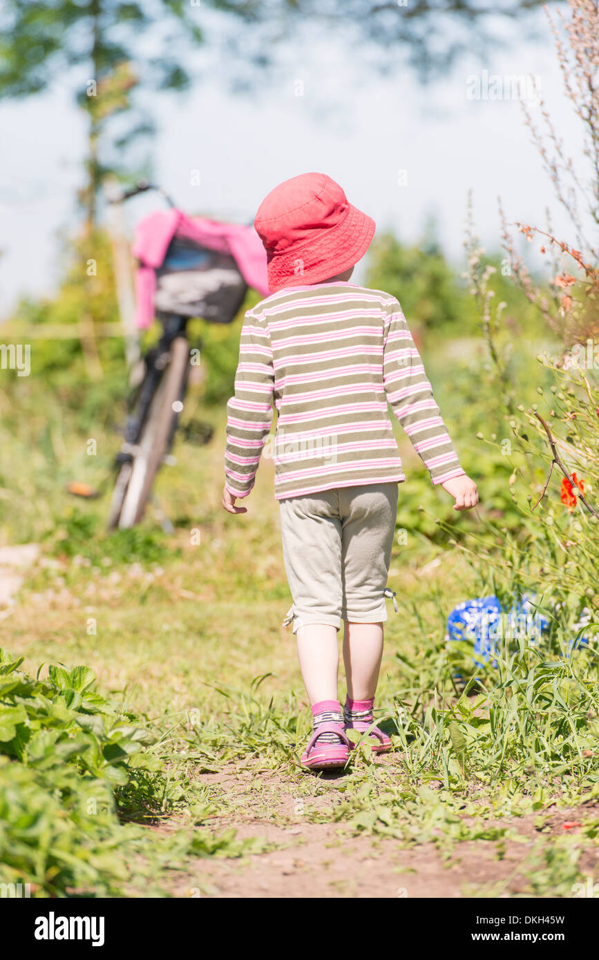 Back view of young child exploring nature, watching green plants and flowers - Stock Image